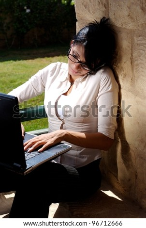 A female working on a lap top in a garden space and talking on a mobile phone - stock photo