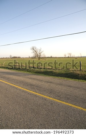 A fence that separates a road and a field. - stock photo