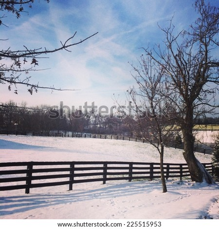 A fenced pasture covered in snow on a winter day. - stock photo
