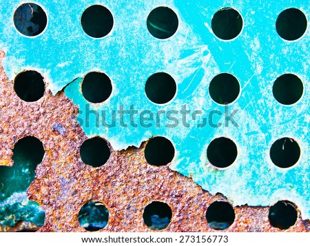 A fenestrated blue metal sheet with rust corrosion - stock photo