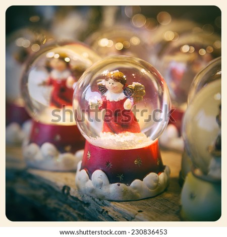 A festive snow globe, containing a cute angel, with bokeh effect background. Processed to look like an aged instant photo. - stock photo