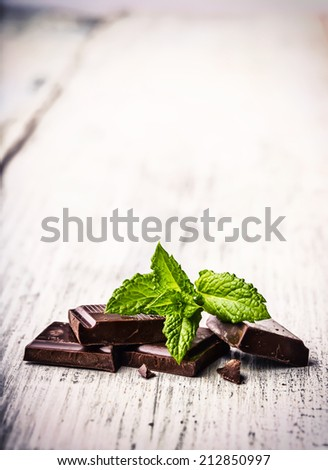 A few cubes of black chocolate with mint leaves on wooden table . - stock photo