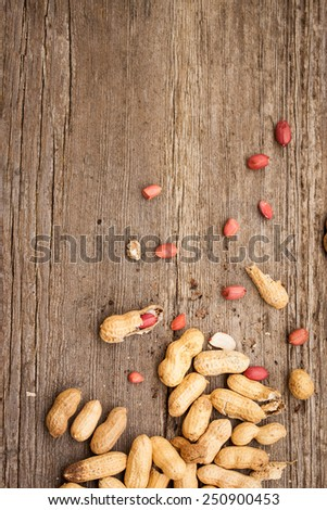 A few peanuts in shells on wood background. Copy space. Also available in horizontal format. - stock photo