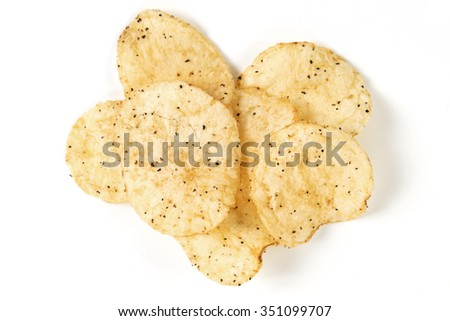 a few sea salt and black pepper kettle cooked potato chips - stock photo