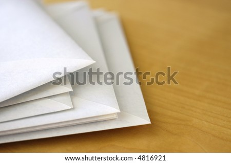 A few white paper envelopes scattered on office desk, shallow focus with large copy space on the right. - stock photo