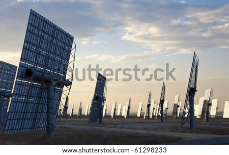 A field of solar mirror panels harnessing the sun's rays to provide alternative green energy - stock photo