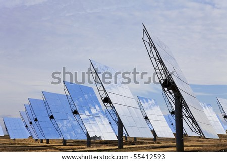 A field of solar mirror panels harnessing the sun's rays to provide renewable alternative green energy - stock photo