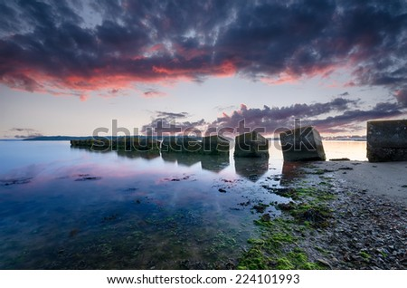 A fiery sunrise over concrete cubes, old WWII tank defenses at Studland beach in Dorset - stock photo