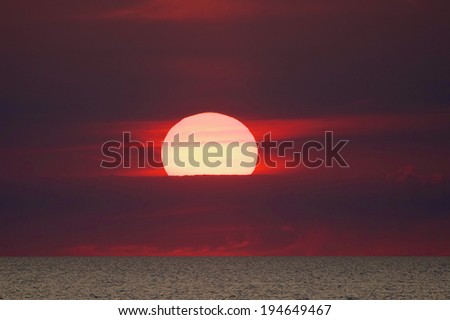 A fiery sunset  A brilliantly colored sunset across a lake. - stock photo