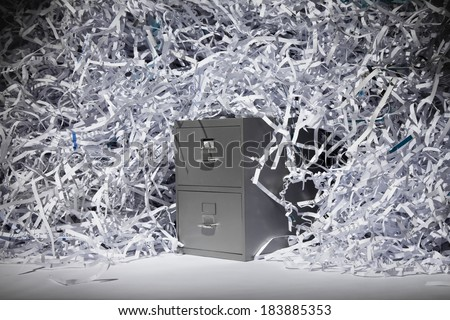 A file cabinet surrounded by a mountain of shredded paper. - stock photo