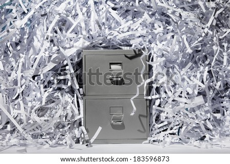 A file cabinet surrounded by lots of shredded paper. - stock photo