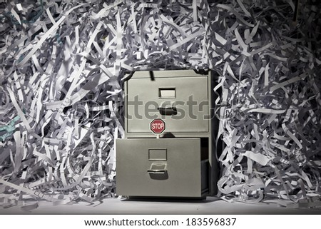 A file cabinet surrounded by lots of shredded paper with a stop sign.  - stock photo