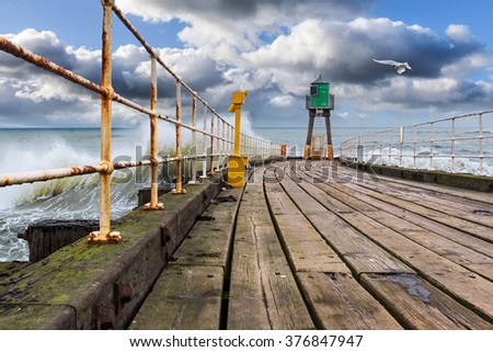 A fine sunny day at the pier with some large waves crashing on the high tide. - stock photo
