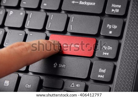 A finger pressing the Enter button on a laptop keyboard, close up shot - stock photo