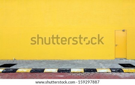 A fire escape door on a blank yellow color sidewall of a building.  - stock photo