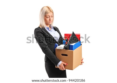 A fired businesswoman in a suit carrying a box of personal items isolated on white background - stock photo