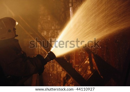 A Firefighter fighting a fire. Nighttime - stock photo