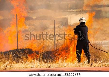 A firefighter preparing the water hose to extinguish a fire in the forest - stock photo
