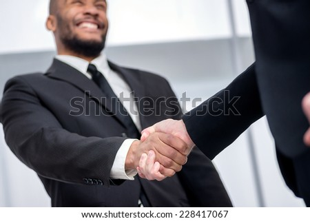 A firm handshake. Two successful smiling businessmen shaking hands with each other while discussing their of business doings. Young people talking in office - stock photo