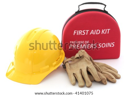 A first-aid kit, hardhat, and gloves spell out the need for safety in the workplace. - stock photo