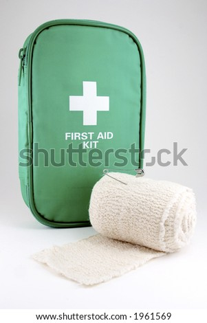 A first aid kit with bandage roll on white - stock photo