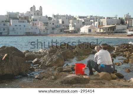 a fisherman cleaning octopus on the shore at naoussa, paros, greece. - stock photo