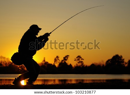 A fisherman fight against a bass at sunset - stock photo
