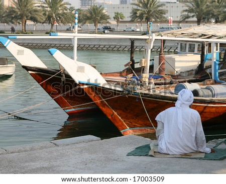 A fisherman sits beside his dhow in Doha, Qatar, during the heat of the day. September 2008 (Ramadan) - stock photo