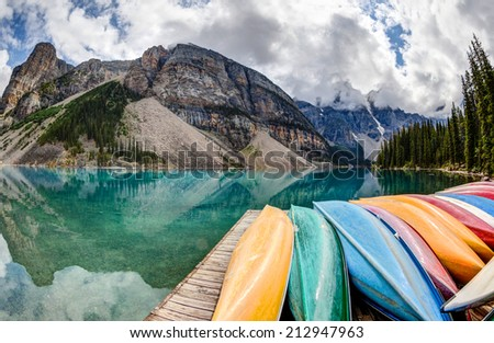 A fisheye view of Moraine Lake in the Canadian Rockies, with vibrant colored canoes on the foreground and the Valley of the Ten Peaks in the background. - stock photo