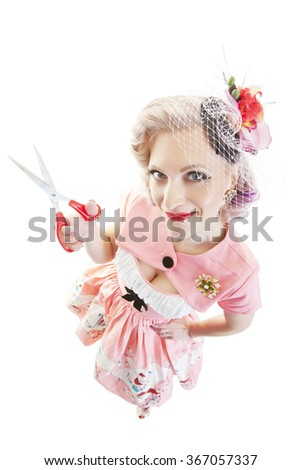 A fisheye view, pretty in pink pinup girl with scissors.  Shot on white background. - stock photo