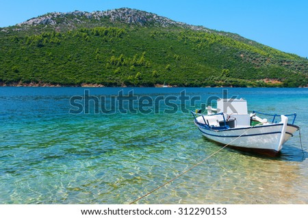 A fishing boat anchored in a small bay - stock photo