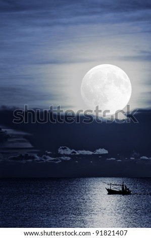 A fishing boat off Thailand returns home under moonlight after setting be it's nets and baskets for the night. - stock photo