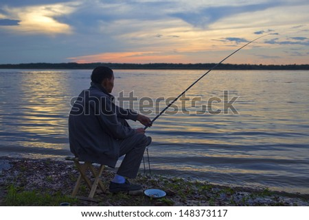 A fishing man at the river bank at sunset in summer - stock photo
