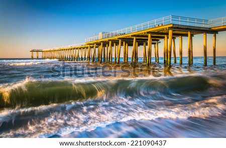 A fishing pier and waves in the Atlantic Ocean at sunrise, in Ventnor City, New Jersey. - stock photo