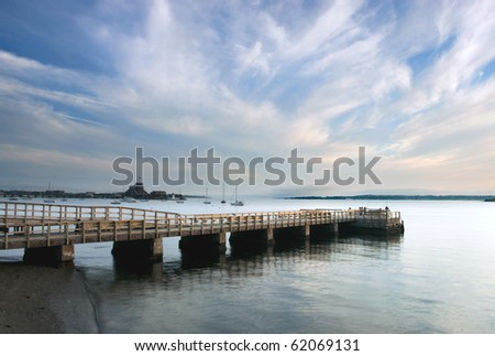 A fishing pier in Newport,RI at sunset on Narragansett Bay - stock photo