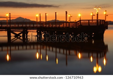 A fishing pier on the bank of the Fraser River near Steveston at first light. Mount Baker, in the Cascade Mountain Range, in the background. Richmond, British Columbia, Canada. - stock photo