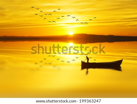 a fishmonger in his traditional boat at sunrise - stock photo