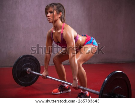 A fit female athlete is lifting weights in a gym. - stock photo