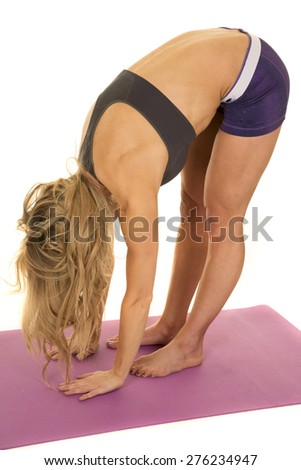 a fit woman bending over stretching her body. - stock photo