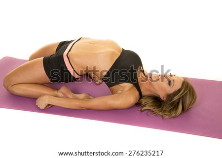 A fit woman doing a yoga stretch, bending her body back. - stock photo