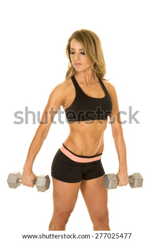 a fit woman in her sports bra and spanks looking over her shoulder while she lifts, weights. - stock photo