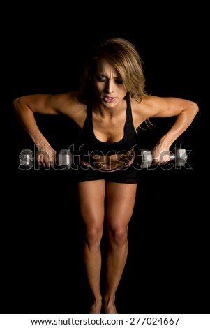 A fit woman leaning over and doing a row to work out her body. - stock photo