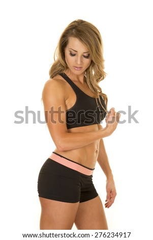 A fit woman looking down at her arm while she is flexing. - stock photo