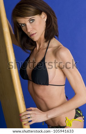 A fit woman stands in swim suit bikini with her well used surfboard  - stock photo