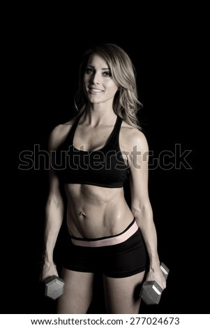 A fit woman with a smile, holding on to her weights. - stock photo