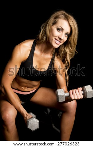 a fit woman with a smile on her face, sitting and doing arm curls with weights. - stock photo