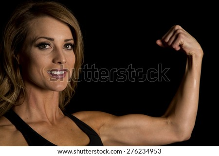 A fit woman with a smile on her face up close, flexing her muscle. - stock photo