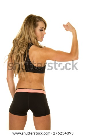 A fit woman with her back to the camera looking at her muscles. - stock photo