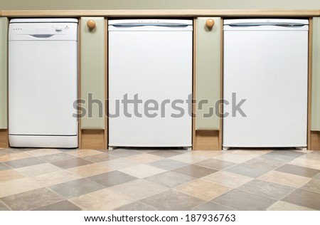 A fitted kitchen with dishwasher,fridge and freezer in a row - stock photo