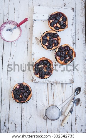 A five delicious homemade cherry and plum tartlets, pie, fruit quiche from above on a country wooden table with powder of sugar and sifter. Rustic style - stock photo